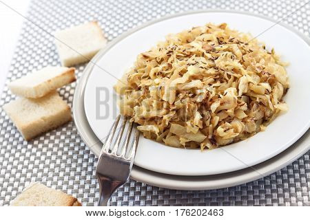 Fried cabbage with caraway and garlic on a plate