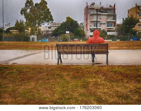 Stranger with a red coat sitting on a bench at a park on a rainy day against a dramatic sky.