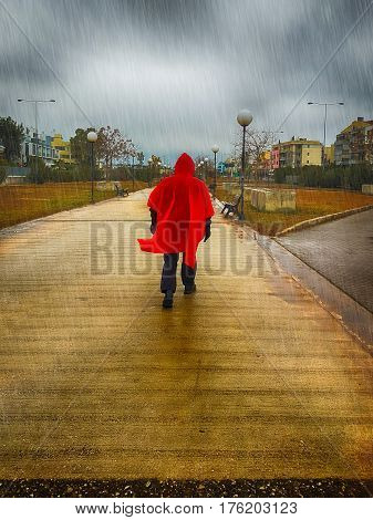 Stranger with a red coat walking at a park on a rainy day against a dramatic sky.
