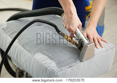 Dry cleaner's employee removing dirt from furniture in flat, closeup