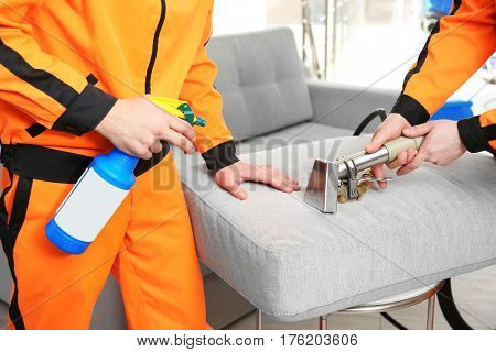 Dry cleaner's employees removing dirt from furniture in flat