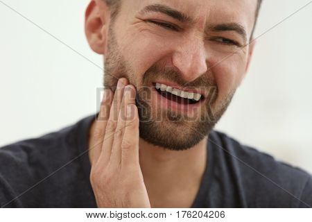 Handsome man suffering from toothache at home, closeup