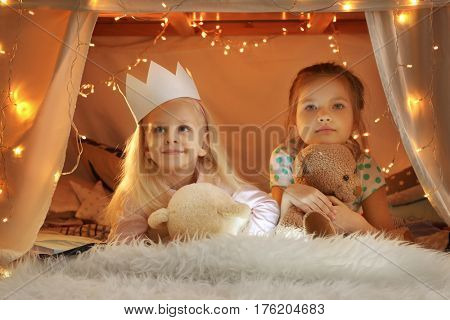 Cute little girls in hovel at home