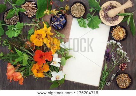 Natural alternative medicine selection with dried and fresh flowers and herbs with hemp notebook on oak background.