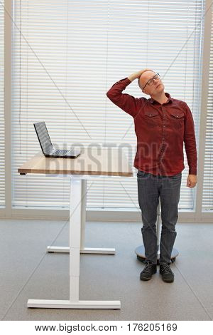 middle age balding man relaxing neck - short break for exercise on chair in office