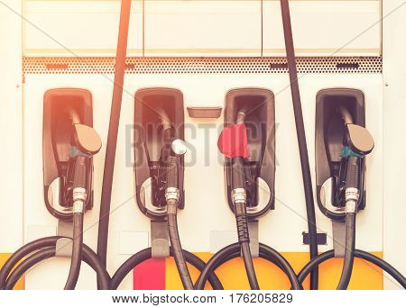 Gasoline nozzle in petrol station service, vintage color tone.