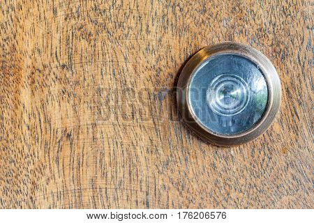 Detail of old lens peephole on wooden door background for security in hotel.