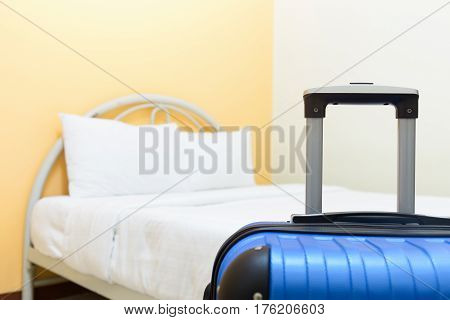 White bed and blue luggage in hotel room.