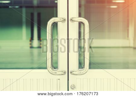 Chrome door handle and glass of aluminium door inside building.