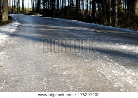 Small icy road on countryside. Focus on foreground,