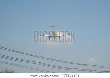 Rear view of a light twin engine propeller aircraft passing over power lines as it approaches the runway.