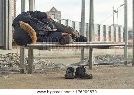 Shot of a drunk male beggar sleeping on the bench of a bus stop in the Moscow street