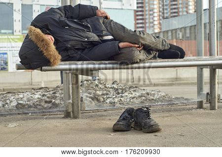Sleeping beggar lying on the bus stop outdoors