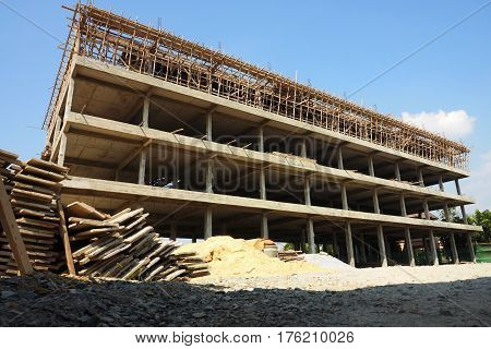 Commercial buildings 4 floors construction around has slam green color background is skies and cloud.