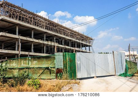 Commercial buildings 4 floors and 10 shop construction has zinc door is closed zinc around has slam green color background is skies and cloud.