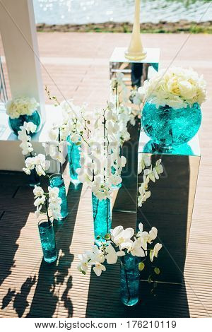 Wedding bouquets of white peon and orchid flowers, in glass vases with blue liquid