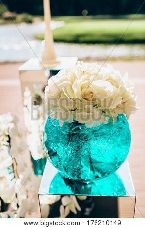 Wedding bouquet of white peon flowers flowers, in glass vase with blue liquid closeup