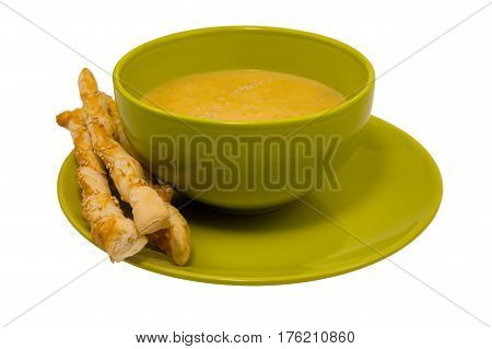 Yellow pumpkin soup in a green plate and crispy italian breadsticks isolated on white