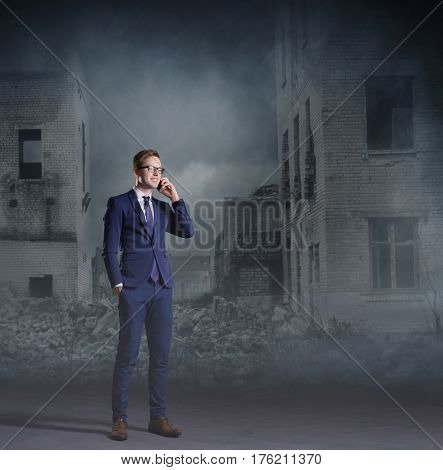 Businessman talking on a mobile phone. Apocalyptic background. Crisis, default, setback concept.