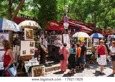 Paris France - Jine 30 2006: Open air artist market at Tertre Square (Place du Tertre) in Montmartre. Tourists considering the menu of a street cafe. Waiters in traditional french costume posing in front of cafe.