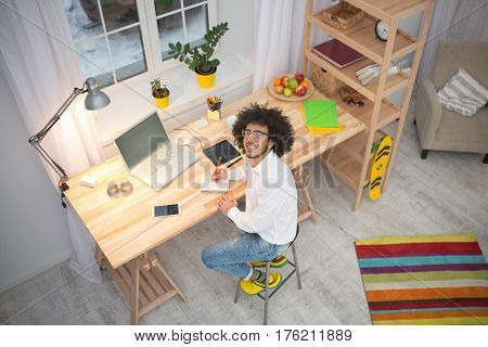 Top view of hipster freelance man working in front of laptop computer at home. Handsome man in glasses looking at camera. Freelance concept. Web designer concept.