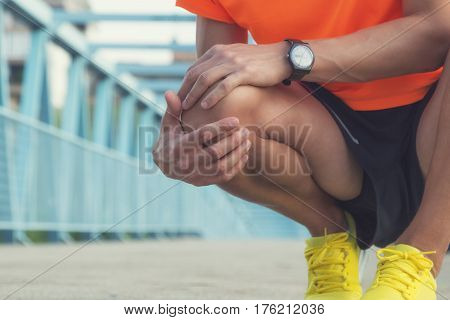 Urban jogger having injury / twisted ankle during exercise.