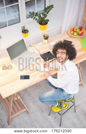 Top view of handsome hipster freelance man in glasses sitting at table and working on laptop computer. Happy man looking at camera while working at home alone.