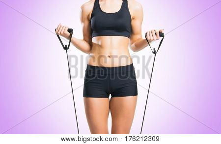 Fit, healthy and sporty woman in sportswear doing expander exercise over violet background.