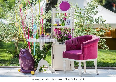 Beautiful unusual wedding decor. Photo zone with whatnot, armchair, table and cat sculpture