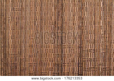 horizontal front view of dark wood sticks texture with black textile bindings
