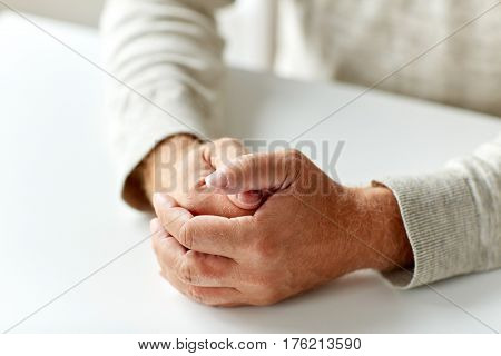 old age, gesture and people concept - close up of senior man hands on table