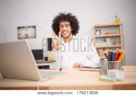 Hipster freelance man showing yo or okay sign to camera while working on laptop computer at home alone. Business or freelance concept.