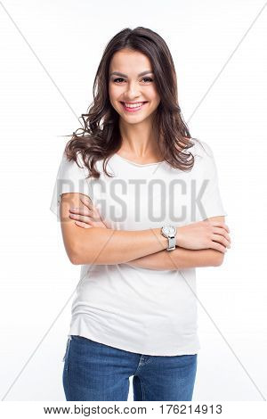 Attractive young woman standing with crossed arms and smiling at camera on white
