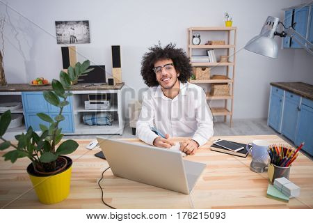 Hipster freelance man smiling for camera while sitting at table and working in front of laptop computer at home alone. Freelance or business concept.