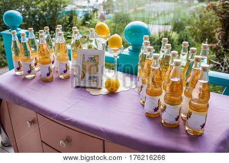 Lemonade table decorated with lemons and photo frame, and a lot of lemonade bottles