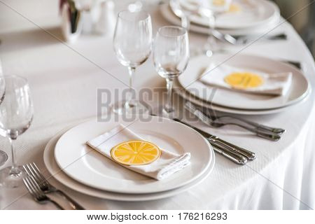 The cute exemple of wedding table serve with white napkin and setting and paper orange