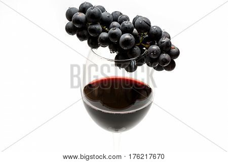 Glass Of Red Wine And Grapes Isolated On White Background