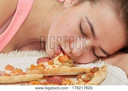 fun sad overeat girl lying with pizza pieces