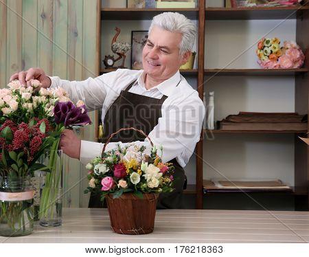 Male florist taking care of flowers in flower shop