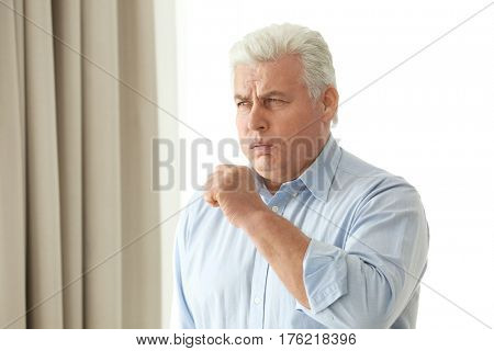 Mature man with allergy at home