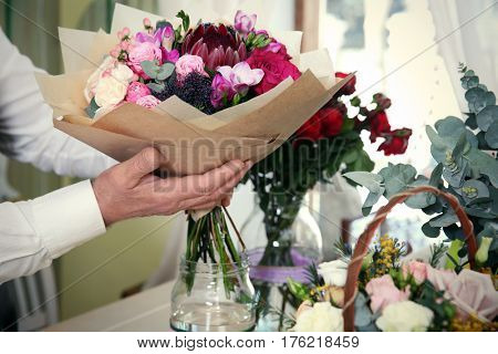 Male florist holding blooming bouquet in flower shop, closeup
