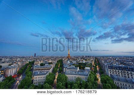 Wide angle skyline of Paris with Champs-Elysees, Montparnasse and Eiffel Tower at sunset with lights