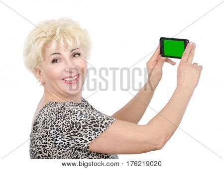 Blonde hair mature woman captures photo by mobile phone with chroma key. Side view of happy woman in leopard print t-shirt with short sleeve. Horizontal mid-shot on white background