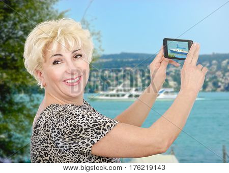 Mature traveling woman captures picture of river boats with cellphone. Smiling blonde hair woman wears leopard print t-shirt with short sleeve. Travel concept. Horizontal mid-shot on blurred river background