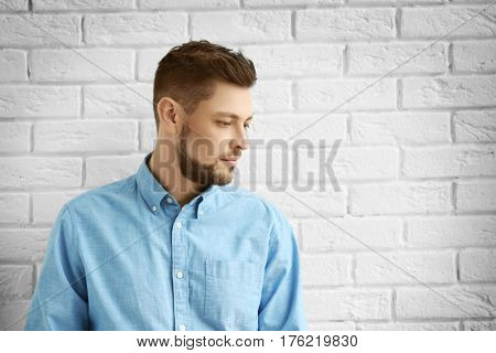 Handsome young man posing on white brick wall background