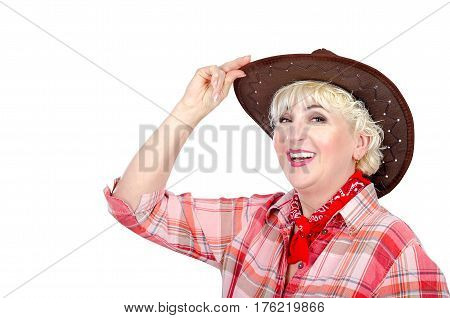 Mature female farmer touches her brown hat with pleasure and shines posing on white background. Cowgirl wears red plaid shirt and neck scarf. Horizontal headshot on white background