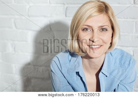 Closeup portrait of happy blonde woman looking at camera.