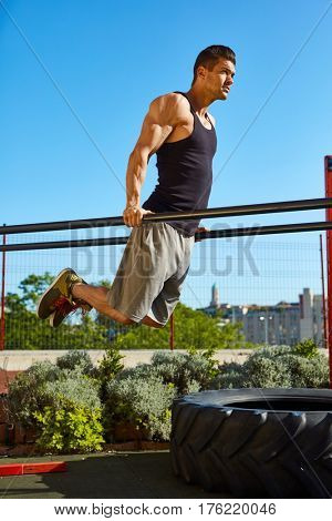Young muscular man working out on the roof of a building.