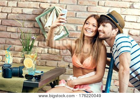 Young loving couple making selfie by mobilephone on summer holiday, smiling happy.