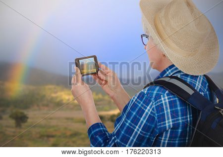Hiking mature woman captures picture of rainbow with cellphone in mountain. Glasses woman tourist with backpack wears blue plaid shirt, yellow hat. Travel concept. Mid shot of back quarter-turn view on blurred landscape background